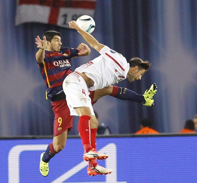 Polský fotbalista v dresu Sevilly Grzegorz Krychowiak (vpředu) v souboji s barcelonským Luisem Suárezem v Superpoháru UEFA.