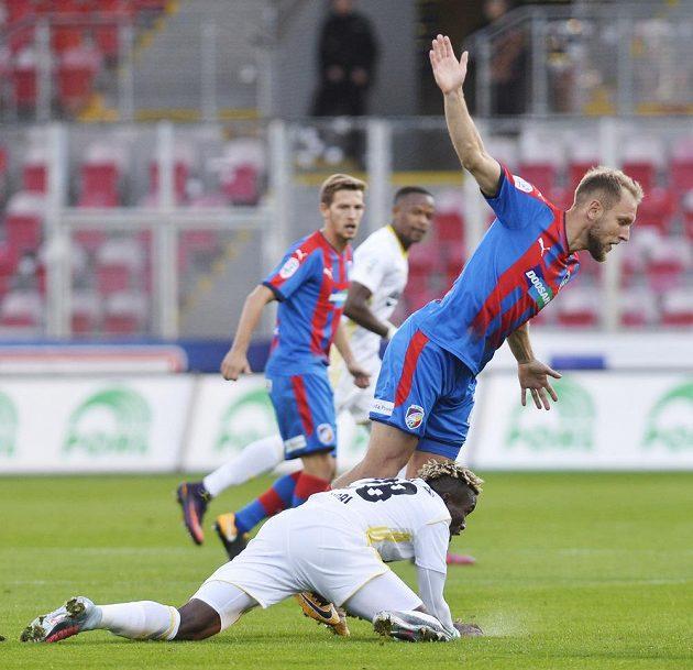 Plzeňský kapitán Daniel Kolář padá po souboji s Ubongem Ekpaiem ze Zlína.