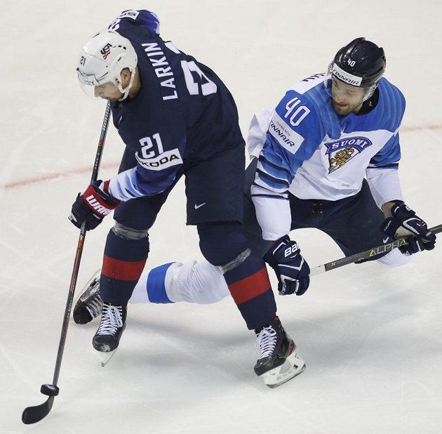 Dylan Larkin z USA v souboji s Petterim Lindbohmem z Finska.
