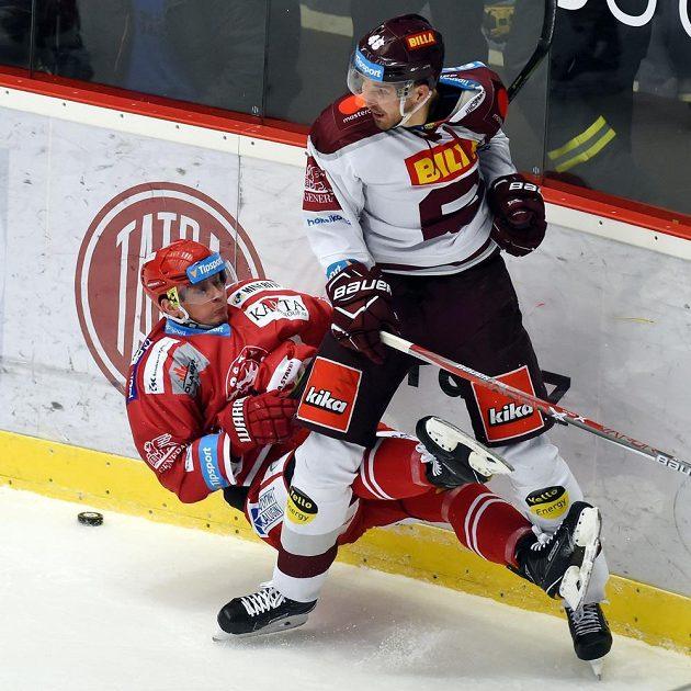 Třinecký Daniel Rákos padá na led po souboji s Petrem Kumstátem ze Sparty.