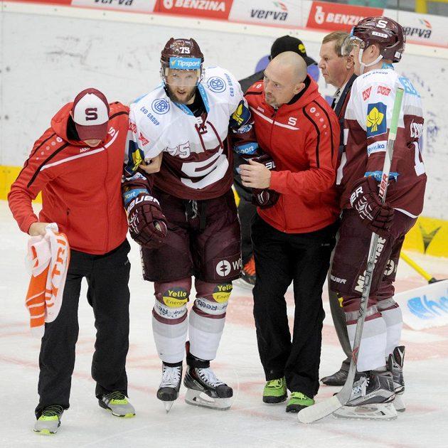 Sparťanský obránce Jan Piskáček je odváděn z ledu po nárazu na mantinel.