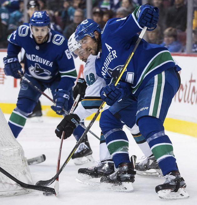 Hokejista Vancouveru Canucks Chris Tanev bojuje o puk s Tomášem Hertlem z týmu San Jose Sharks.