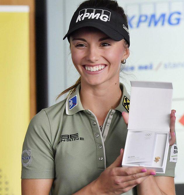 Klára Spilková pózuje s olympijským účastnickým odznakem.