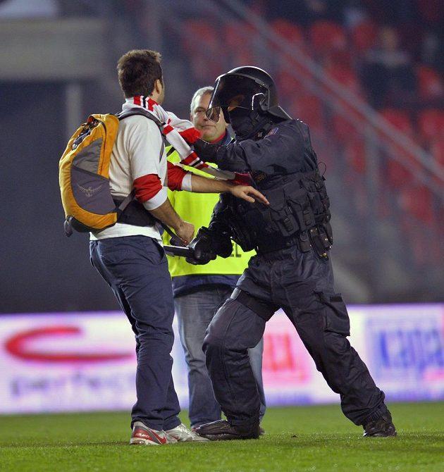 Policejní těžkooděnci zasahují proti fanouškům Slavie, kteří po skončení zápasu vnikli na hřiště.