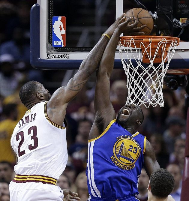 LeBron James z Clevelandu se snaží prosadit, brání mu Draymond Green z Golden State.