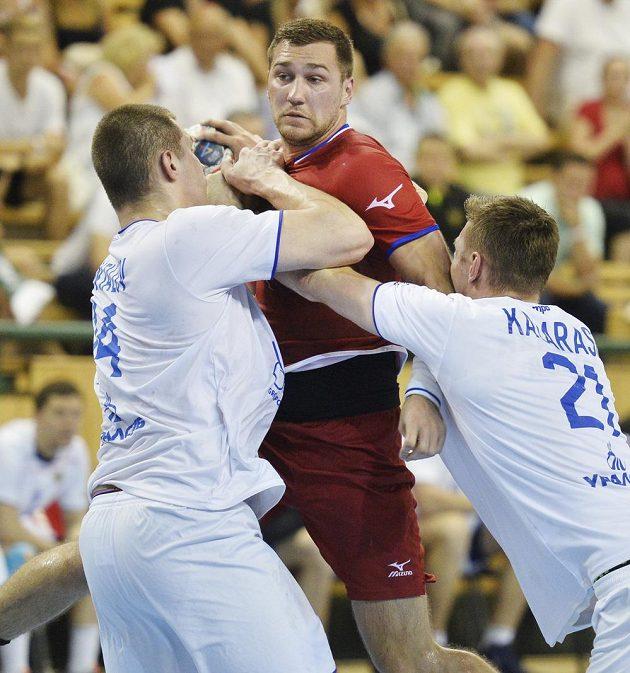 Český hráč Tomáš Babák se snaží prosadit mezi Dmitrijem Santalovem (vlevo) a Glebem Kalarašem z Ruska v úvodním utkání play off kvalifikace mistrovství světa házenkářů.