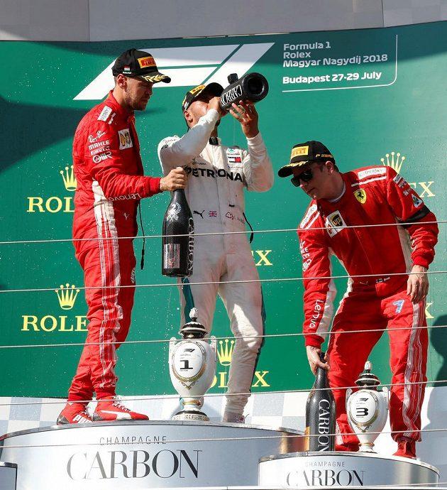 Lewis Hamilton z Mercedesu slaví, doprovází ho konkurence z Ferrari Sebastian Vettel (vlevo) a Kimi Räikkönen.