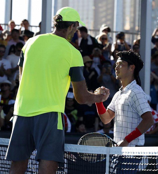 211 cm vysoký Ivo Karlovič si podává ruku s více než o 30 cm menším Japoncem Sugitou po vzájemném zápase ve 2. kole Australian Open.
