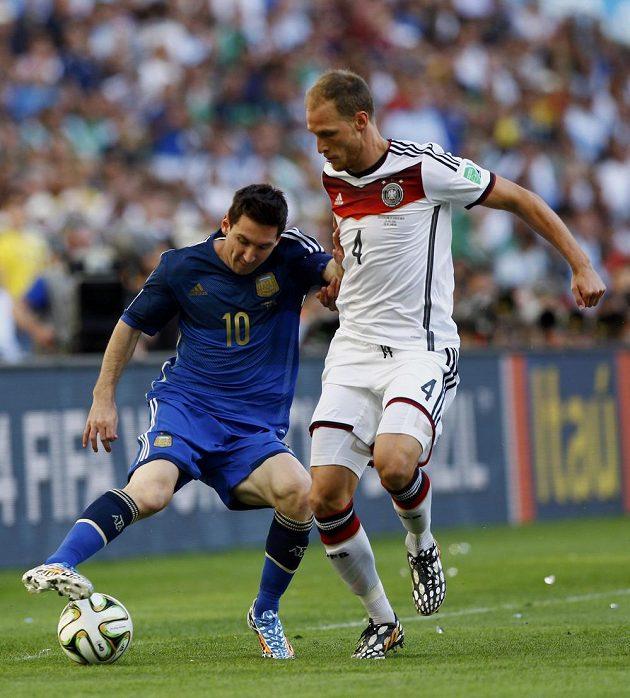 Německý obránce Benedikt Höwedes v souboji s Argentincem Lionelem Messim.