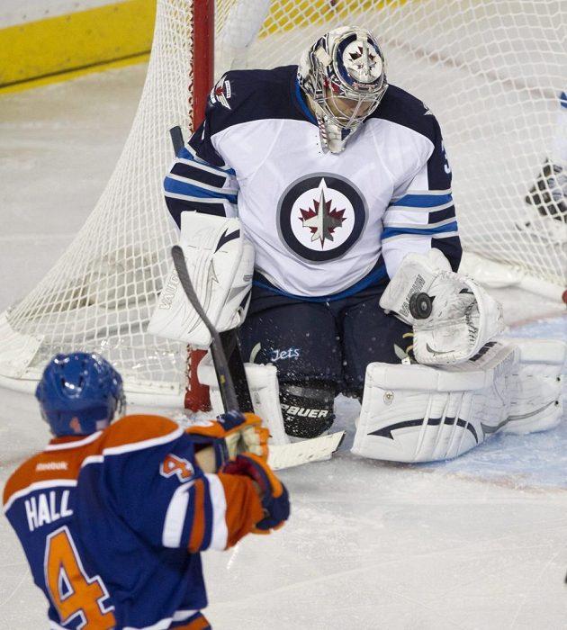 Brankář Winnipegu Ondřej Pavelec (v bílém dresu) likviduje šanci Taylora Halla z Edmontonu.