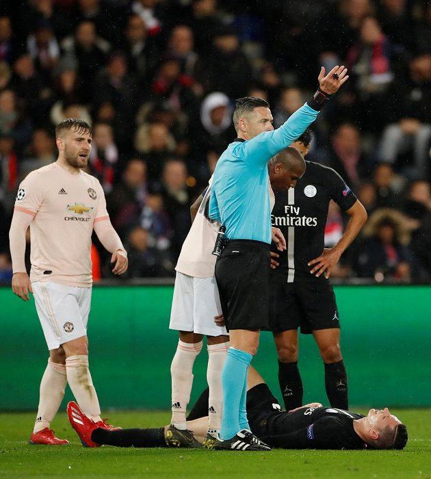 Zraněný Julian Draxler z PSG zůstává ležet, sudí Damir Skomina mu přivolává pomoc.