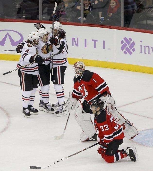 Hokejisté Chicaga slaví vítěznou branku v prodloužení Arťoma Anisimova (15) v zápase proti New Jersey.
