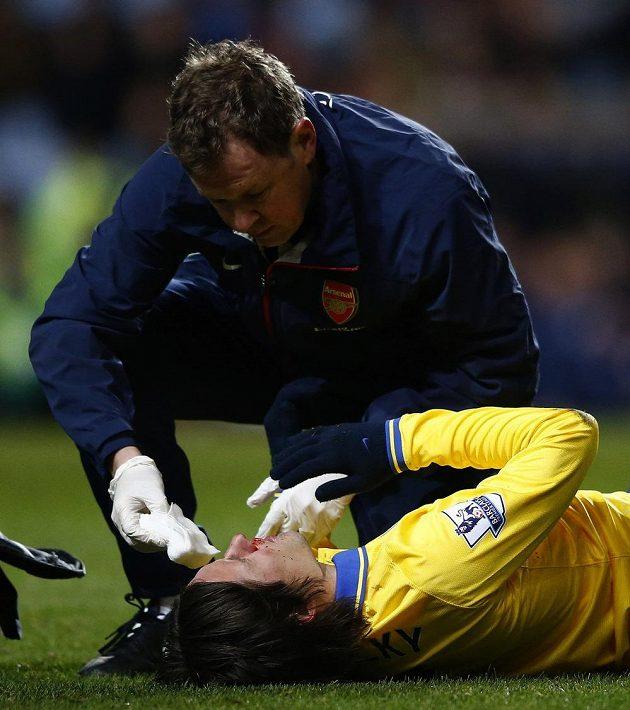 Tomáše Rosického ošetřuje lékař Arsenalu v zápase s Aston Villou.