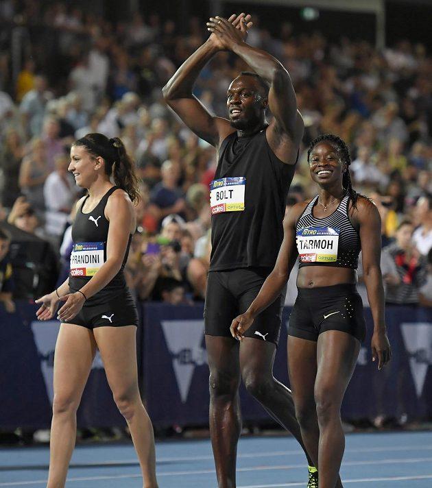Usain Bolt slaví triumf ve smíšené štafetě na 4x100 m s partnerkou Jennou Prandiniovou z USA. Vpravo je Jeneba Tarmohová.