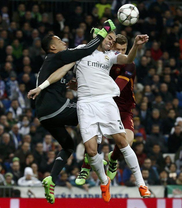 Brankář Realu Madrid Keylor Navas vyráží míč, ve vzdušném souboji Pepé s Edinem Džekem z AS Řím.