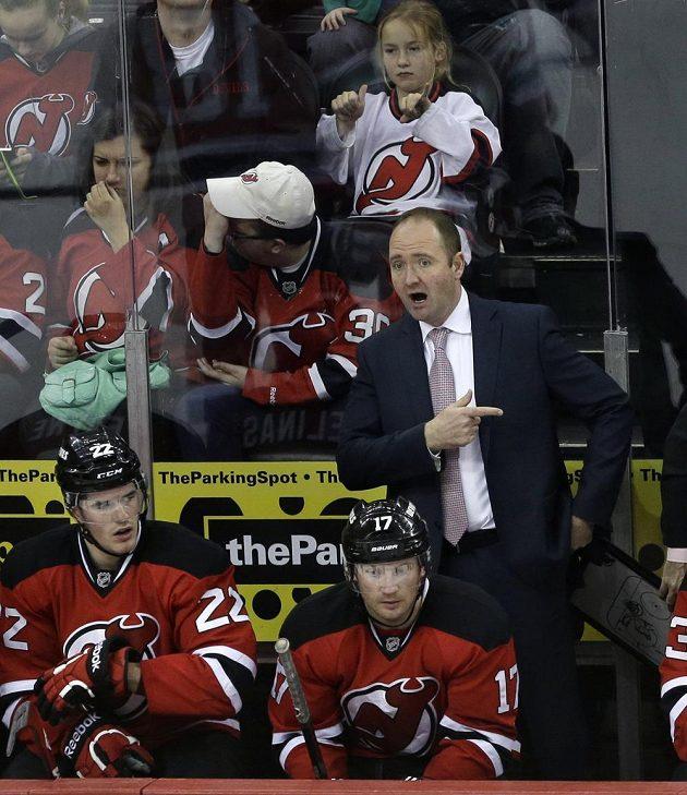 Trenér hokejistů New Jersey Peter DeBoer (vzadu) během utkání s Calgary.