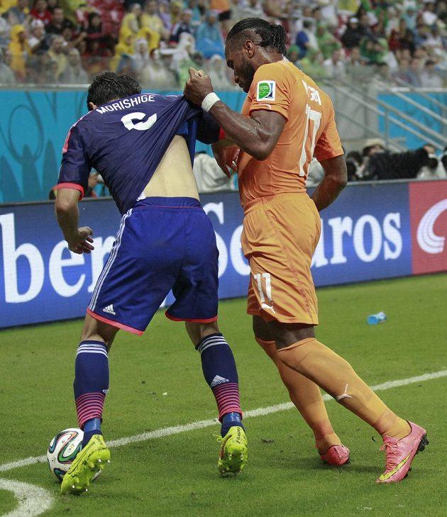 Didier Drogba si pomáhá nedovoleným způsobem proti soupeři.