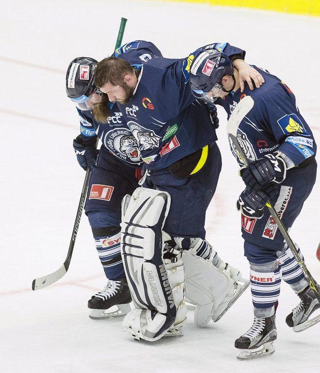 Zraněný brankář Liberce Ján Lašák opouští v doprovodu spoluhráčů ledovou plochu.