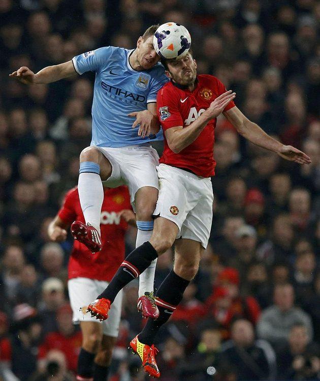 Střelec úvodního gólu derby Edin Džeko (vlevo) z Manchesteru City v hlavičkovém souboji s Michaelem Carrickem z United.