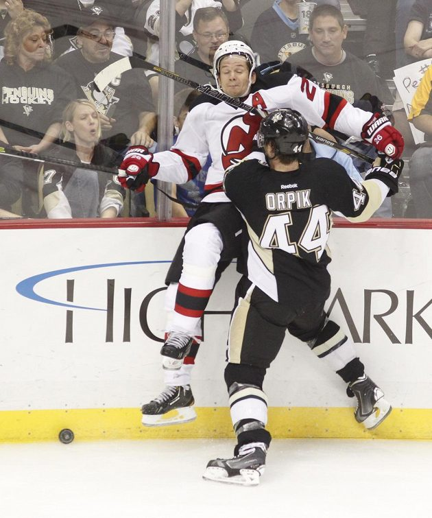 Brooks Orpik z Pittsburghu naráží na mantinel Patrika Eliáše z New Jersey Devils.