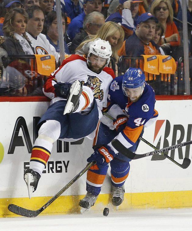 Jaromír Jágr (vlevo) a obránce New York Islanders Calvin de Haan bojují o puk.