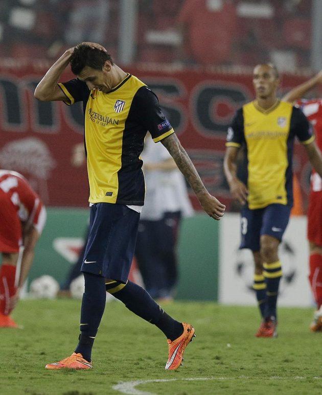 Smutný útočník Atlétika Madrid Mario Mandžukič opouští trávník po porážce s Olympiakosem.