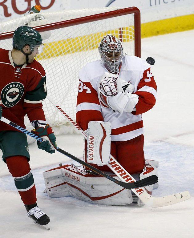 Brankář Detroitu Petr Mrázek zasahuje v zápase proti Minnesotě. Vlevo je útočník Wild Jason Zucker.
