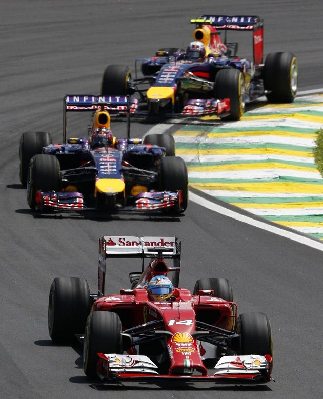 Španělský pilot Fernando Alonso z Ferrari před dvojicí jezdců Red Bullu.