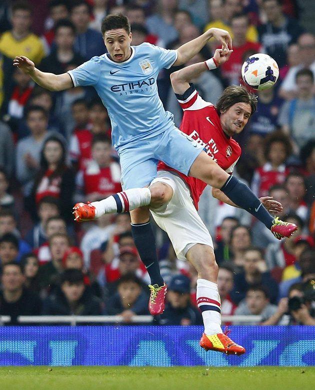 Samir Nasri z Manchesteru City v hlavičkovém souboji se svým bývalým spoluhráčem Tomášem Rosickým z Arsenalu.