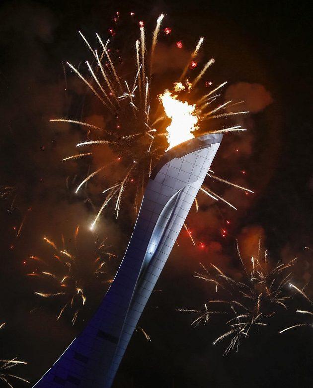 Ohňostroj u příležitosti slavnostního zahájení ZOH v Soči, v popředí pylon s olympijským ohněm.