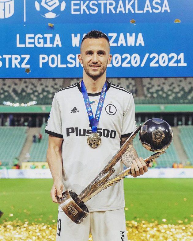 Útočník Legie Varšava s pohárem pro vítěze polské ligy 2020/2021.