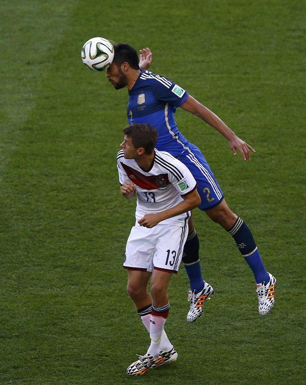 Argentinský obránce Ezequiel Garay (v modrém dresu) hlavičkuje před německým útočníkem Thomasem Müllerem ve finále MS.