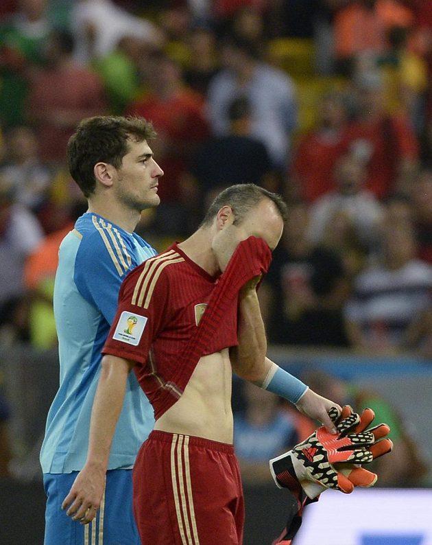 Zklamaní brankář Iker Casillas a záložník Andrés Iniesta opouští po výprasku od Chile trávník slavného brazilského stadiónu Maracaná.