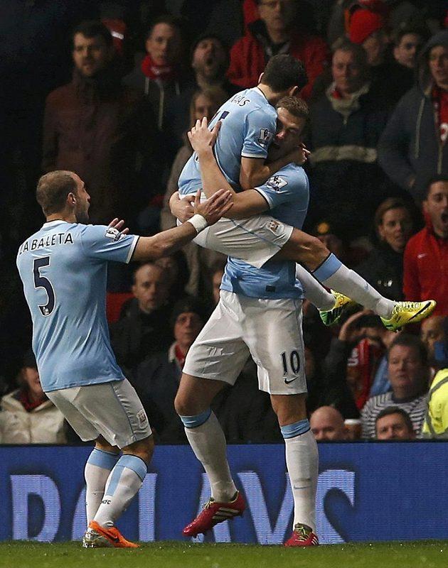 Fotbalisté Manchesteru City Edin Džeko (vpravo) a Jesús Navas se radují ze vstřelení gólu proti Manchesteru United. Vlevo přibíhá spoluhráč Pablo Zabaleta.
