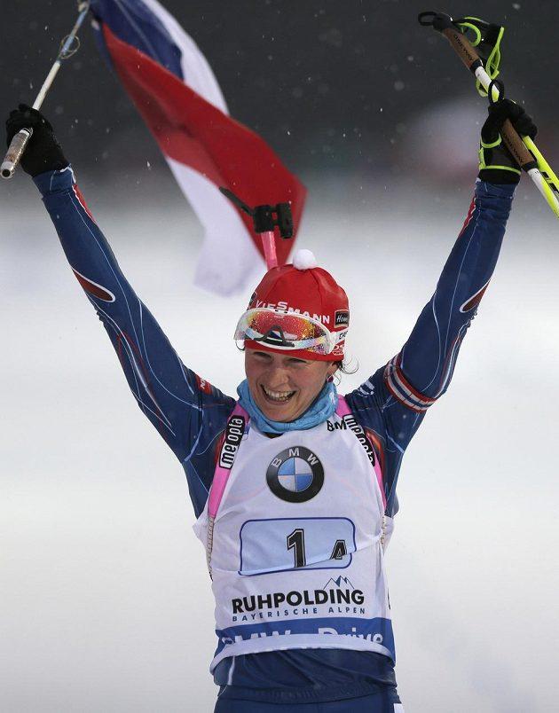 Biatlonistka Veronika Vítková slaví s vlajkou vítězství české štafety v Ruhpoldingu.