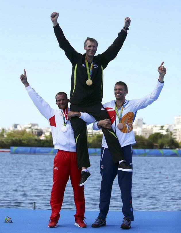 Stříbrný Damir Martin (vlevo) a bronzový Ondřej Synek zvedají nad hlavu olympijského vítěze Mahého Drysdalea.