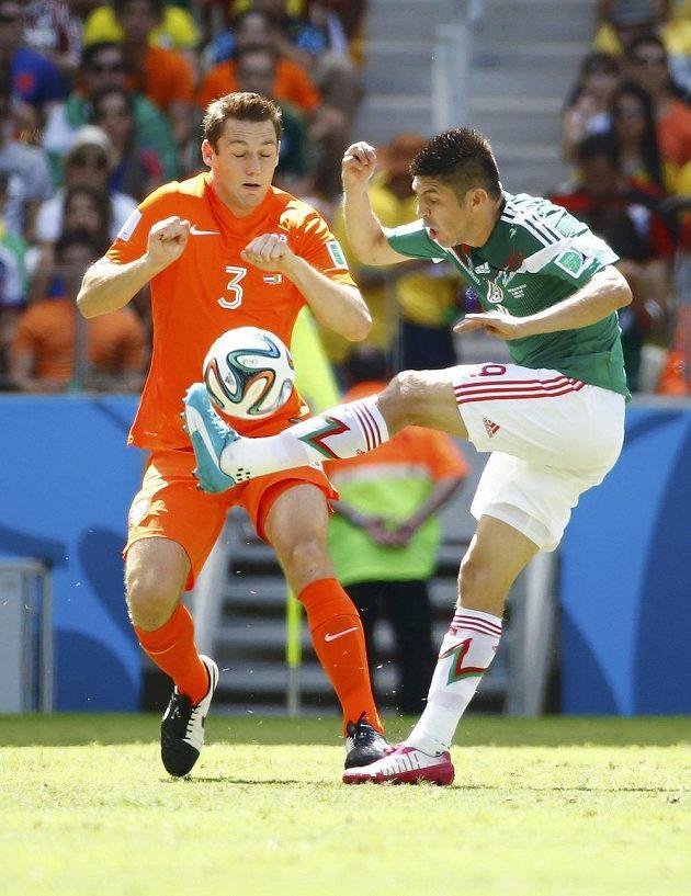 Mexičan Oribe Peralta (vpravo) odehrává míč před Stefanem de Vrijem z Nizozemska.