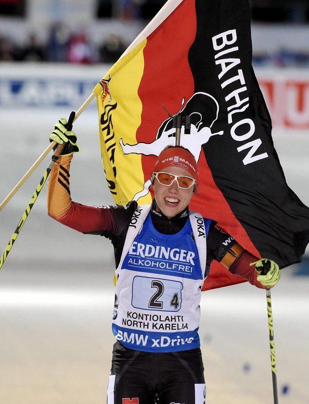 Německá biatlonistka Laura Dahlmeierová slaví s vlajkou vítězství ve štafetě.