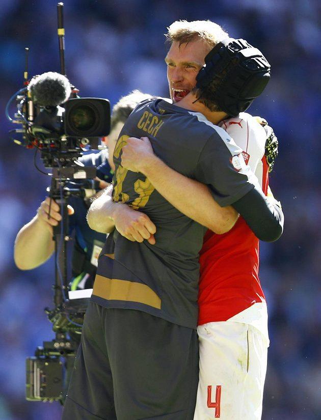 Obránce Arsenalu Per Mertesacker a brankář Petr Čech se objímají po vítězství nad Chelsea.