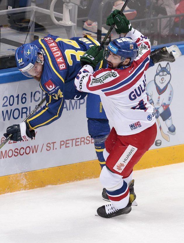 Český hokejista Milan Gulaš v souboji u mantinelu s Jonasem Junlandem ze Švédska.