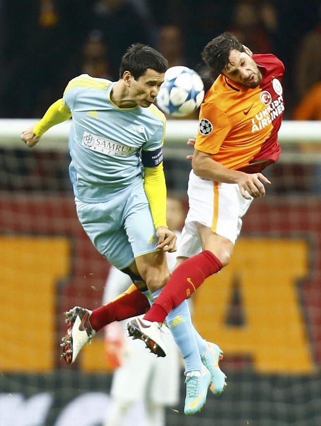 Hakan Balta z Galatasaraye a Foxi Kethevoama z Astany v hlavičkovém souboji o balón.