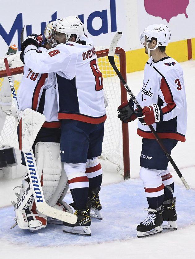 Hvězdný ruský útočník Washingtonu Capitals Alex Ovečkin (8) slaví se spoluhráči výhru nad týmem New York Islanders.