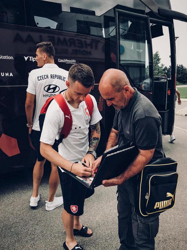 Jan Sýkora rozdává autogramy po příjezdu do Rakouska, v pozadí Patrik Schick.