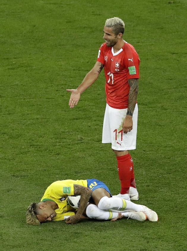 Jen se na něj podívejte! Švýcar Valon Behrami se podivuje nad ležícím Brazilcem Neymarem.
