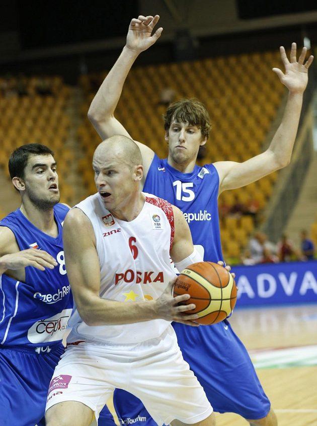 Polský basketbalista Maciej Lampe (uprostřed) se snaží prosmýknout mezi Tomášem Satoranským a Janem Veselým (vpravo).