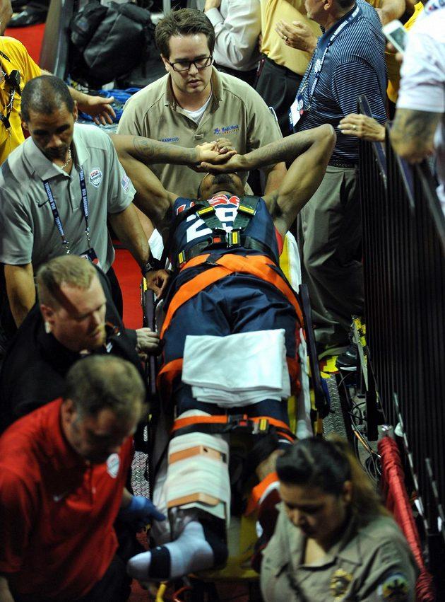 Medici se starají o zraněného basketbalistu George během exhibice v Las Vegas.