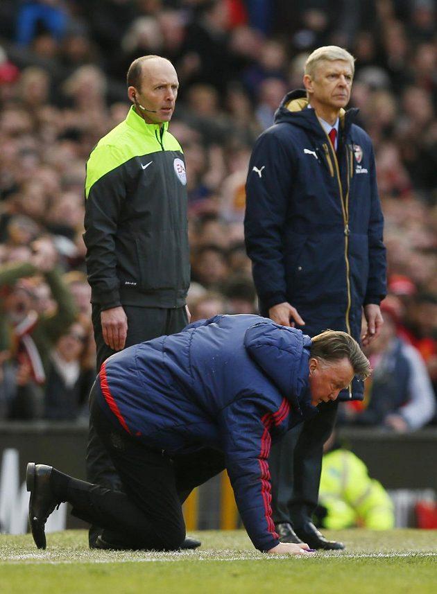Kouč Manchesteru United Louis van Gaal se ztěžka zvedá, za ním vlevo je čtvrtý rozhodčí Mike Dean a trenér Arsenalu Arséne Wenger.