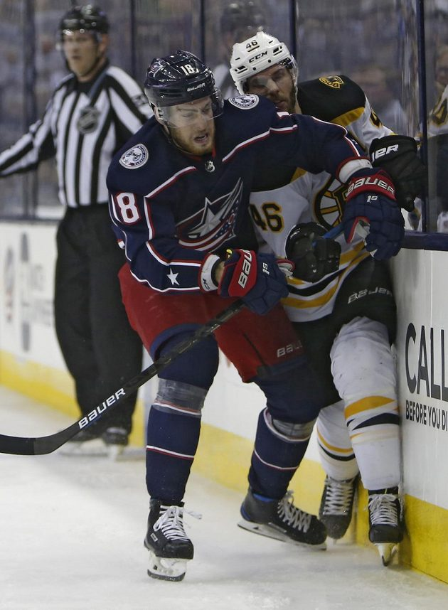 Hokejista Columbusu Blue Jackets Pierre-Luc Dubois v souboji s českým útočníkem Bostonu Davidem Krejčím během utkání play off NHL.