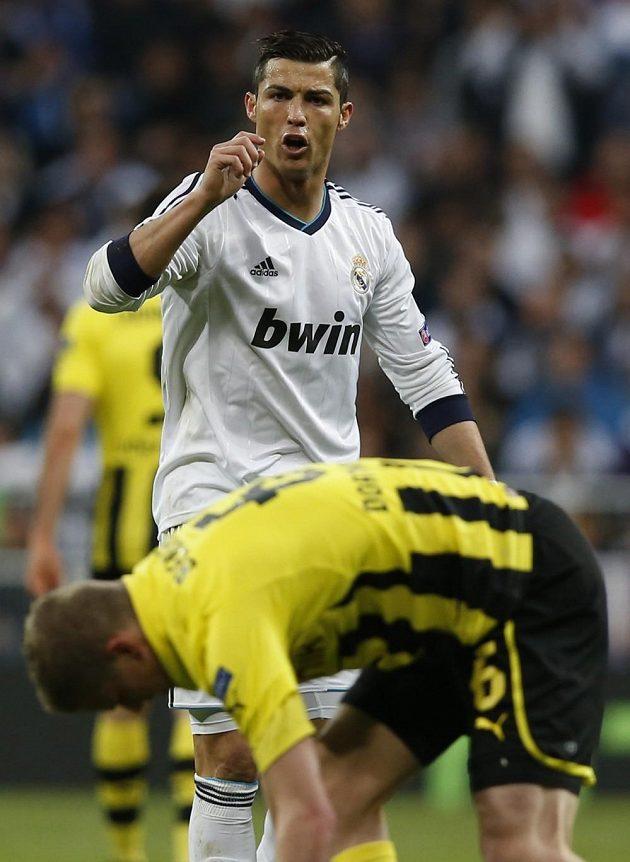 Cristiano Ronaldo z Realu gestikuluje po střetu se Svenem Benderem z Borussie Dortmund.