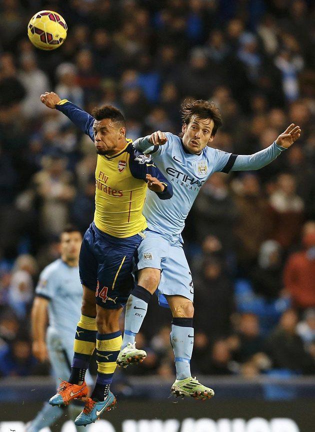 Záložník Arsenalu Francis Coquelin ve vzdušném souboji s Davidem Silvou z Manchesteru City.